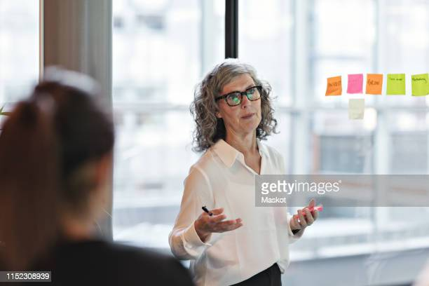 senior confident businesswoman giving presentation in board room at office - weibliche angestellte stock-fotos und bilder