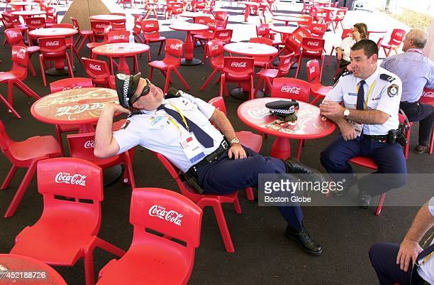 Senior constable Howard Simcock of the New South Wales Police takes a break with senior constable Greg Callander right under a concession tent that's...
