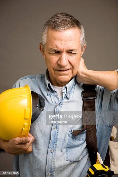 Senior construction worker holding hard hat hand behind neck