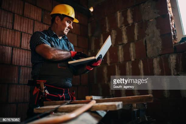 Leitende Bauarbeiter mit einem laptop