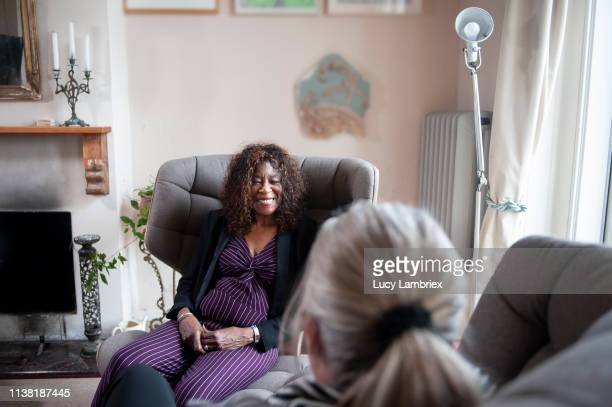 senior counselor listening to and smiling at her client - lucy lambriex stockfoto's en -beelden