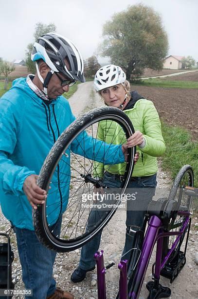 """senior couple adjusting wheel of cycle on dirt road, bavaria, germany"" - partire bildbanksfoton och bilder"