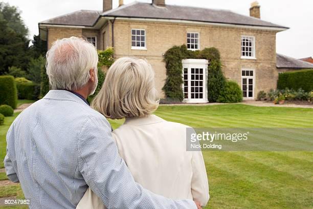 Senior couple admiring house.
