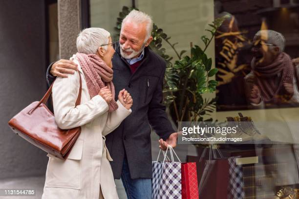 senior couple admiring shop merchandise through the store window - spending money stock pictures, royalty-free photos & images
