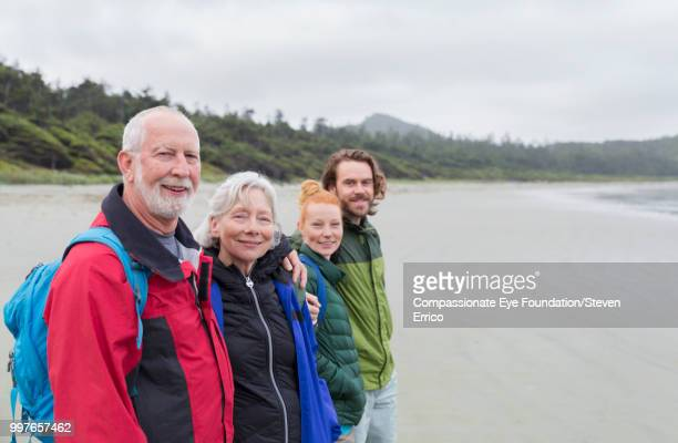 Senior couple and adult children hiking on beach looking at ocean view