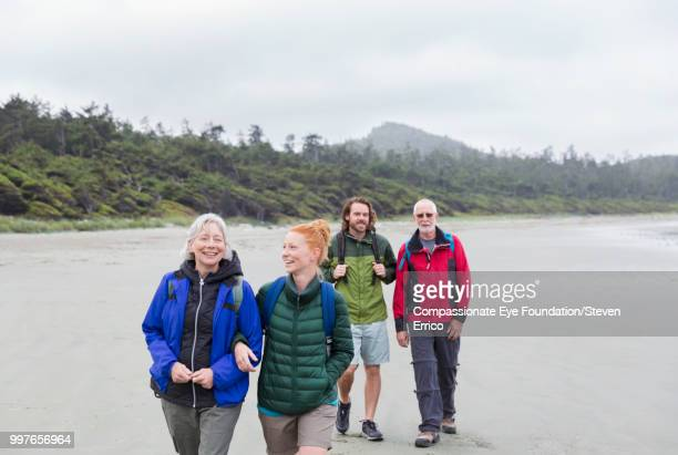 """senior couple and adult children hiking on beach - """"compassionate eye"""" stock pictures, royalty-free photos & images"""