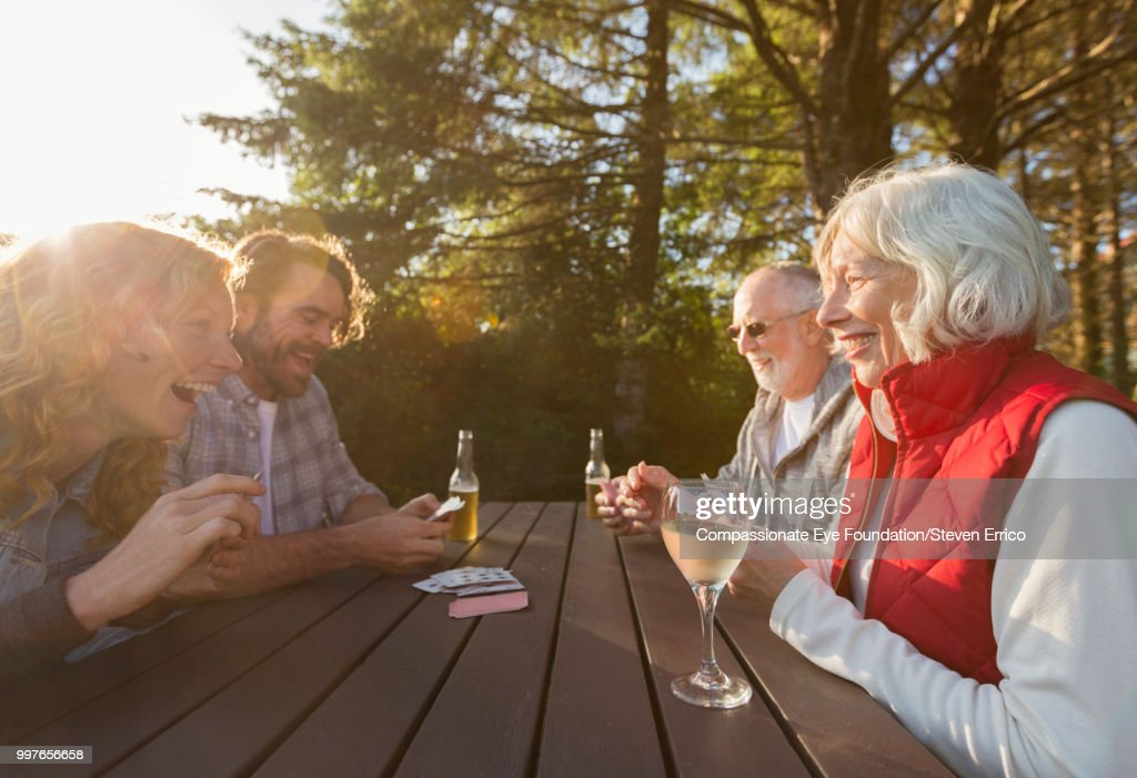 Senior couple and adult children playing cards at campsite picnic table : Stock Photo