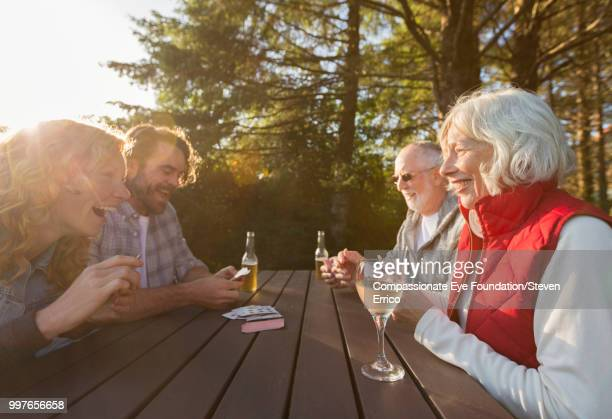Senior couple and adult children playing cards at campsite picnic table