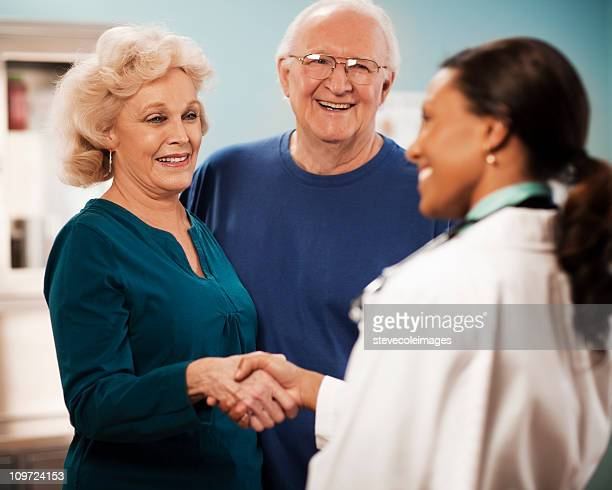 Senior Couple and Doctor Shaking Hands
