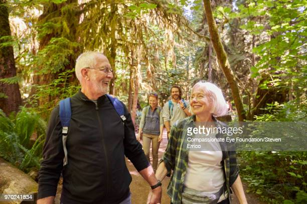 Senior couple and family hiking in forest