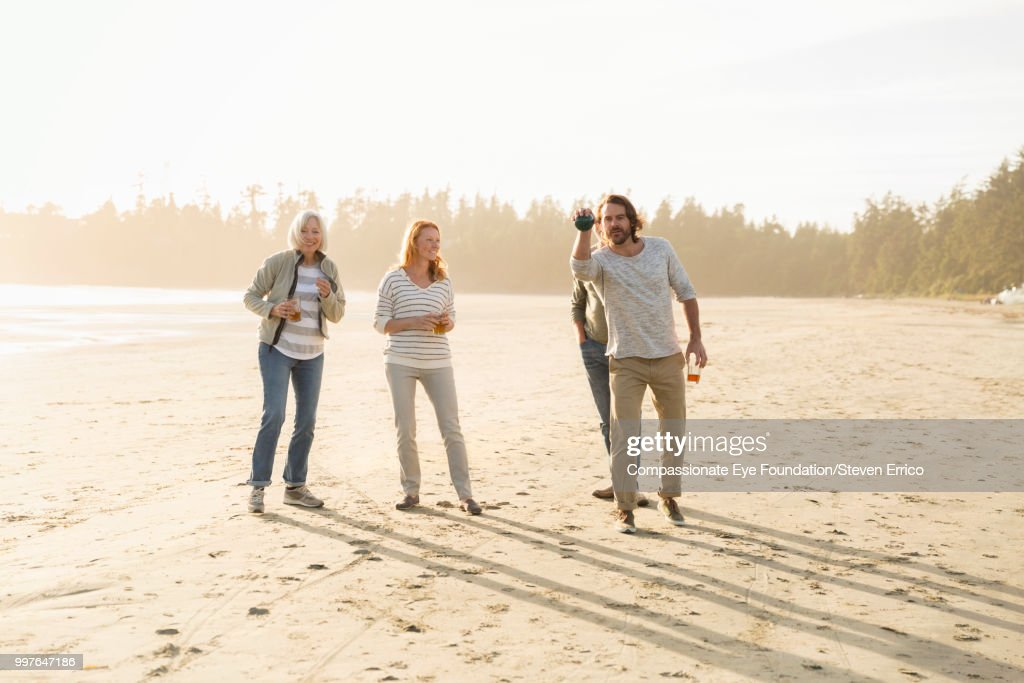 Senior couple and family playing boules on beach at sunset : Stock Photo