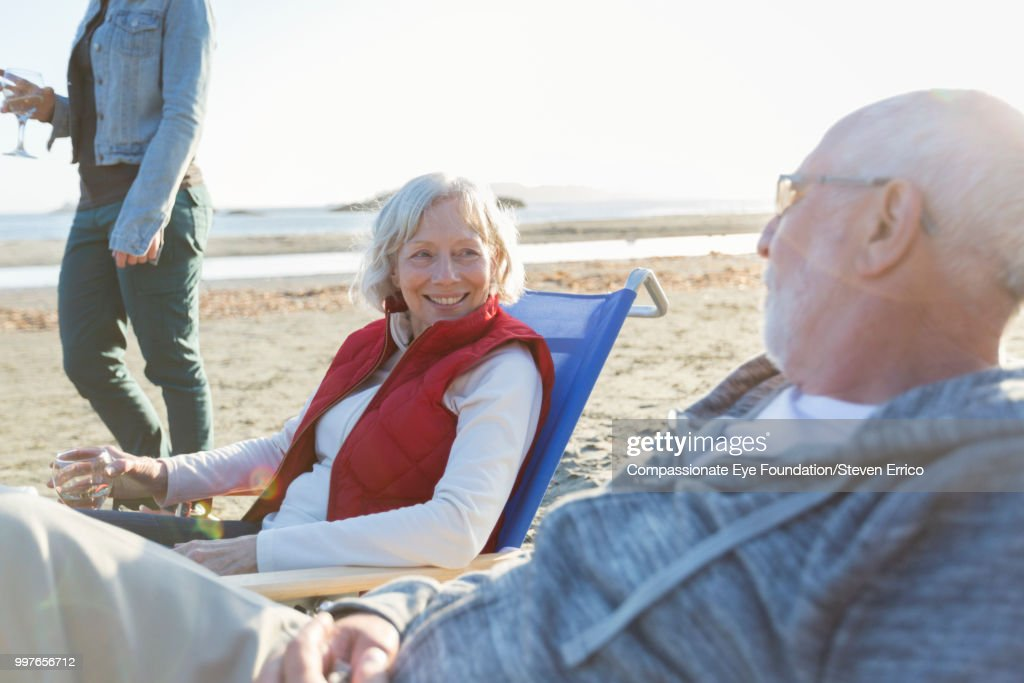 Senior couple and family relaxing on beach at sunset : Stock Photo