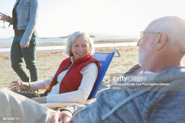 Senior couple and family relaxing on beach at sunset