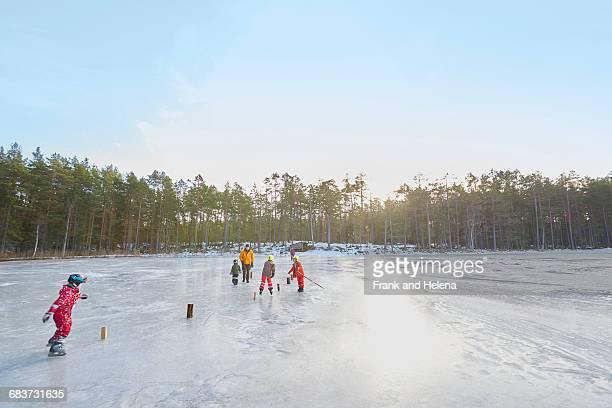 Senior couple and grandchildren practicing ice skating slalom on frozen lake, Gavle, Sweden