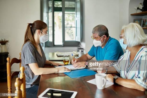 書類に署名するマスクのシニアカップルと保険代理店 - 加入 ストックフォトと画像