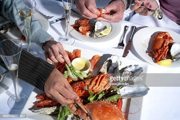 Casal Idoso e Casal tendo marisco almoço, close-up