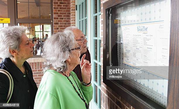 senior couple and mature woman reading outdoor restaurant menu - pre labeled stock pictures, royalty-free photos & images
