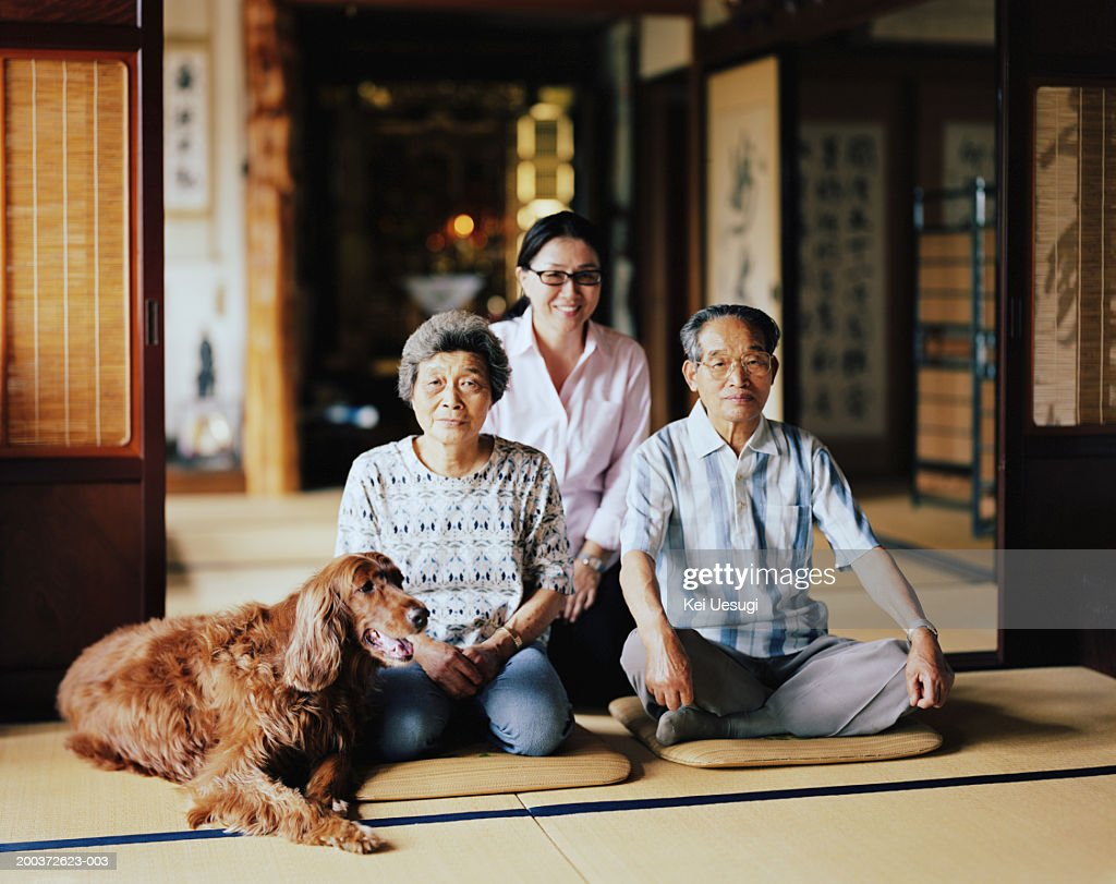 Senior couple and mature woman siting in temple with dog, portrait : Stock Photo