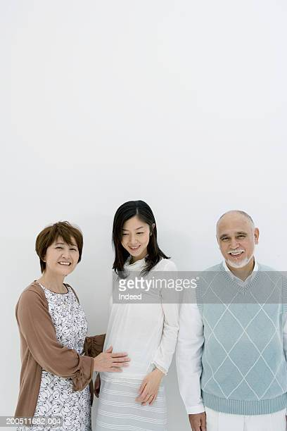 Senior couple and pregnant adult daughter smiling, portrait