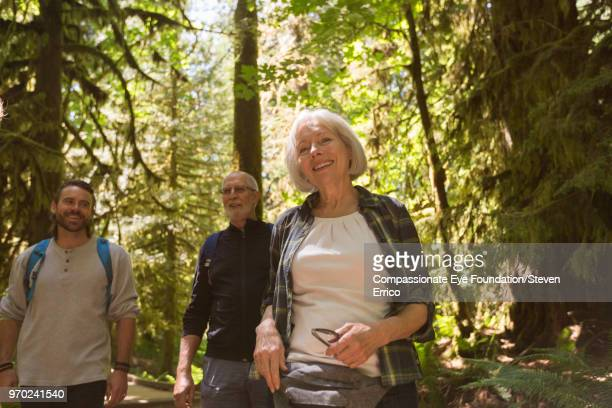 Senior couple and son hiking in forest