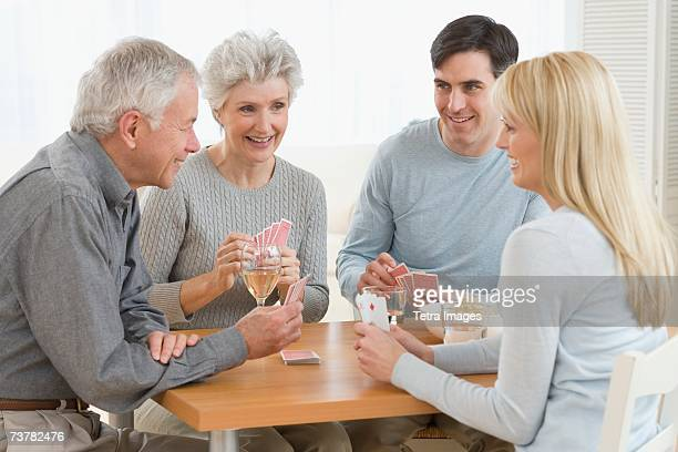 senior couple and young couple playing cards - mother in law stock pictures, royalty-free photos & images