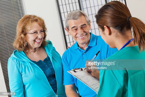 Senior couple answering questions as nurse fills out patient chart