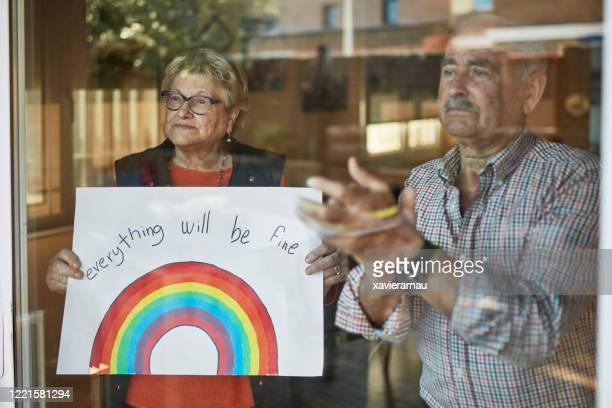 senior couple applauding and showing a hand drawn rainbow at home in quarantine - nhs stock pictures, royalty-free photos & images