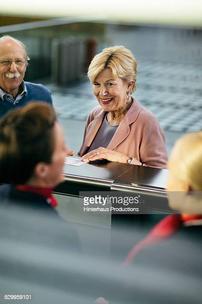 Senior Couple At Airport Check-In Counter