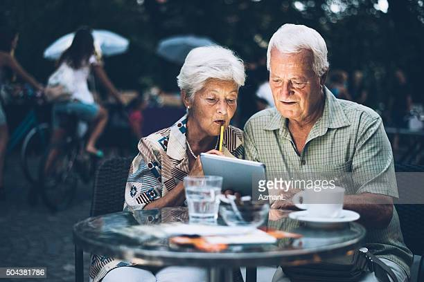 Senior couple at cafe in the evening using digital tablet