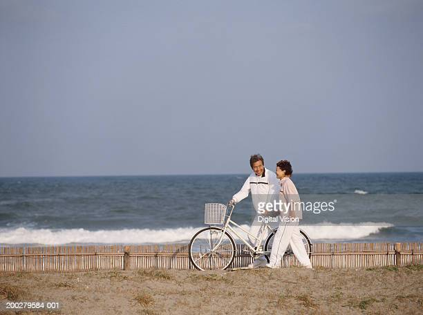 Senior couple at coast walking with bicycle