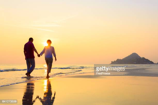 senior couple at golden beach - shadow forms stock photos and pictures