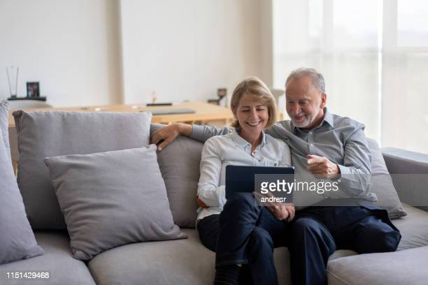 senior couple at home going online on a digital tablet - diabetic amputation stock pictures, royalty-free photos & images