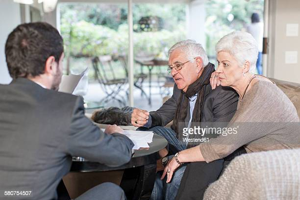 Senior couple at home having a meeting with salesman