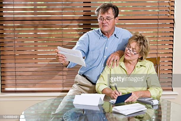 Senior couple at home reviewing finances, paying bills together