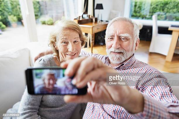 Senior couple at home taking cell phone picture