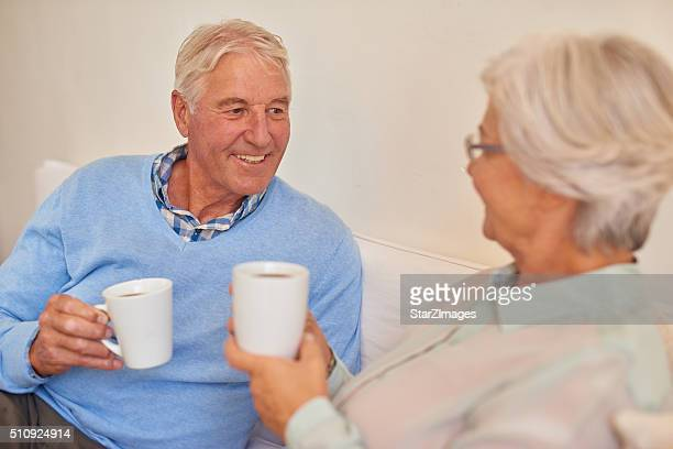 Senior couple at home together drinking morning tea