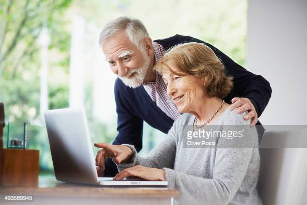 senior couple at home using laptop - processo de envelhecimento - fotografias e filmes do acervo
