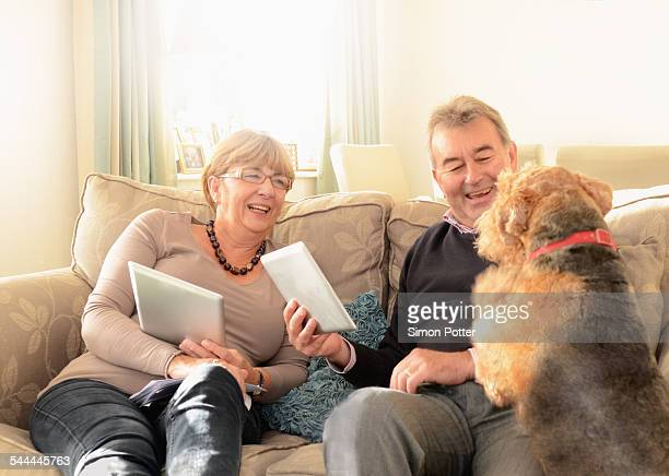 Senior couple at home with dog, using digital tablets