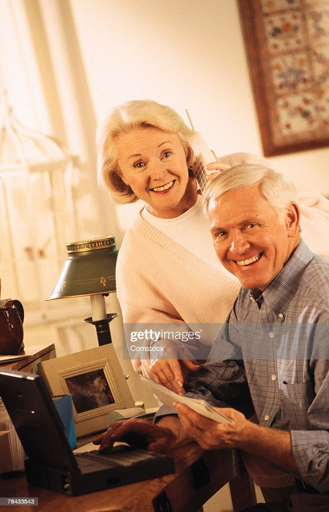 Senior couple at home with laptop computer : Stockfoto
