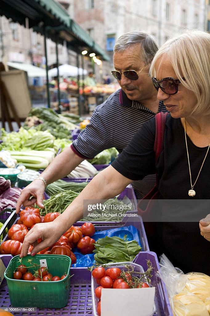 Senior couple at market buying vegetables : Foto stock