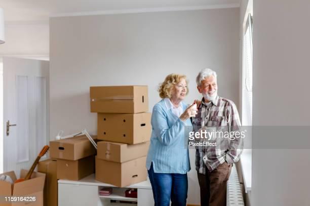 窓越しに見る引っ越し日のシニアカップル - 引っ越し ストックフォトと画像