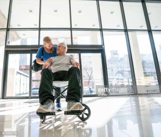 Senior couple at the hospital and man sitting on a wheelchair while partner hugs him