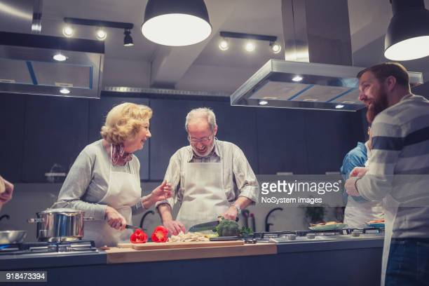 Senior couple, attendees of cooking class, chopping vegetables