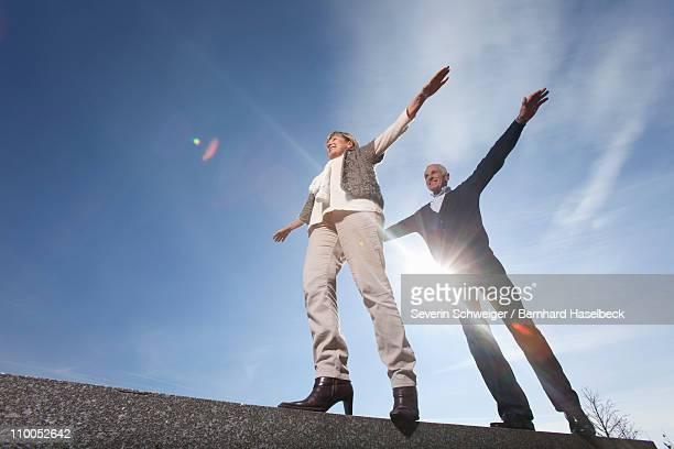 Senior couple balancing along a wall
