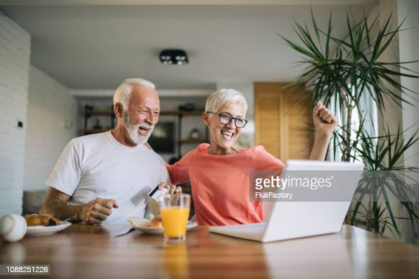 senior couple bidding on an online auction - bid stock pictures, royalty-free photos & images