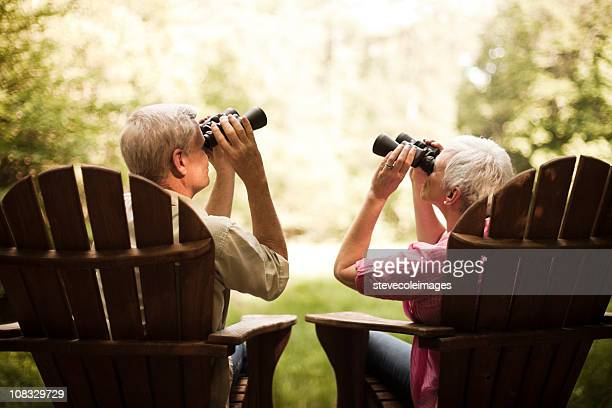 Senior Couple Birdwatching on a Wood Deck