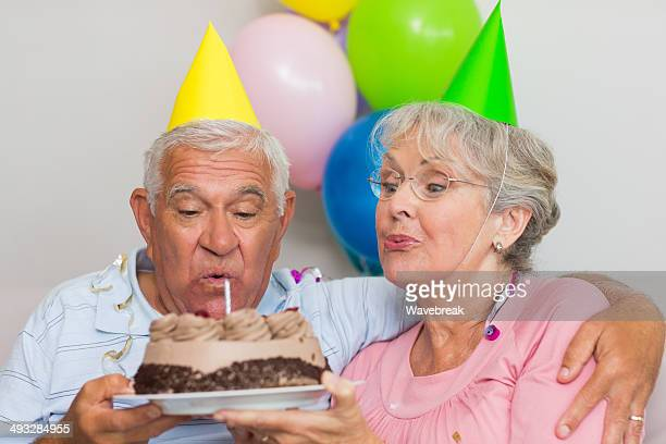 Senior couple blowing out candles on birthday cake