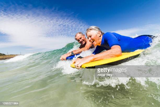 senior couple bodyboarding together - exhilaration stock photos and pictures