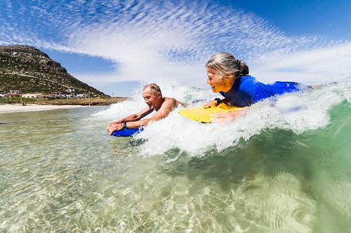 Senior couple bodyboarding together - gettyimageskorea