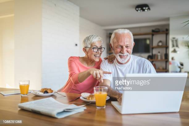 senior couple booking their flight back to home - human body part stock pictures, royalty-free photos & images
